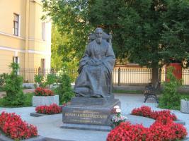 Памятник Иоанну Кронштадтскому перед входом в дом